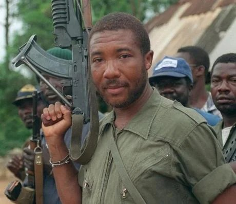 An assault rifle-toting Charles G. Taylor as a rebel leader in Liberia in 1990.